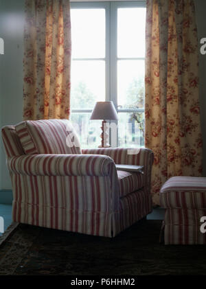 Striped armchair and stool in front of window with floral curtains in country living room - Stock Photo