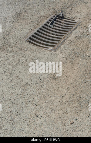 Drainage grille on a country lane. Metaphor 'down the drain'. - Stock Photo