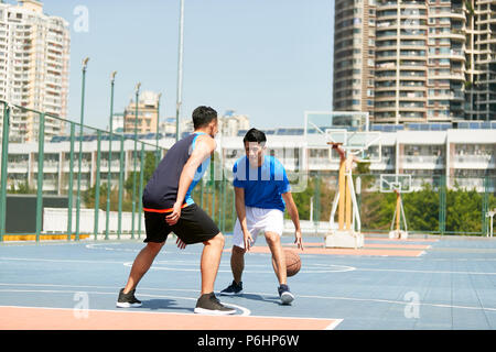 young asian male basketball player playing one-on-one on outdoor court. - Stock Photo
