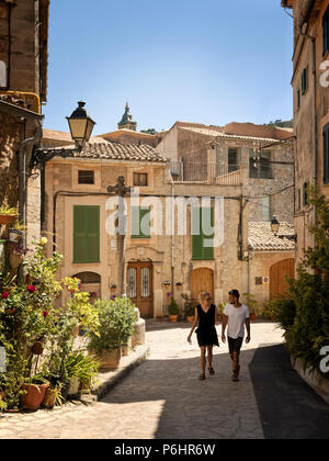 A young man and woman walk through old Valldemossa, near the old village cross, which was constructed in the 18th century to mark the boundaries of th - Stock Photo