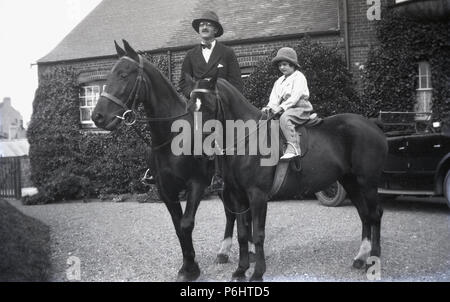 1930s, England, an aristocratic father and his young daughter sitting on their horses on the gravel driveway of their country house. The gentleman is wearing a blazer and bow tie for his ride, while the young girl holds onto the reins. - Stock Photo