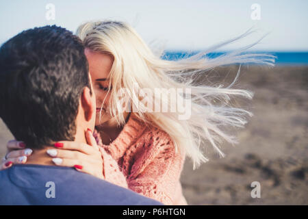 romantic couple in love hugging and kissing with closed eyes and full of emotion. beautiful couple in tenderness together outdoor leisure activity at  - Stock Photo