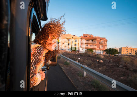 beautiful lady caucasian with nice smile travel in a black car looking the sun of sunset and enjoy the warm season. summer time for model traveling wi - Stock Photo