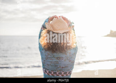 freedom young woman with cowboay hat in front of the ocean enjoying vacation and outdoor lifestyle. summer sunlight and waves and traveler spirit - Stock Photo