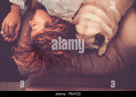 friendship and relationship concept with young beautiful woman and nice pug dog sleeping together on the bed in the morning. closer with love and swee - Stock Photo