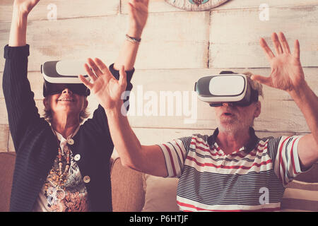 couple of senior adult caucasian enjoy technology with goggled headset and play in virtual realuty together having fun at home. trying new experience  - Stock Photo