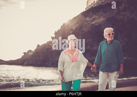 happy senior adult couple in love waing and smiling enjoying the summer time on the beach and the retired lifestyle of their new life together after y - Stock Photo
