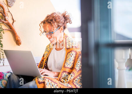 beautiful smiled caucasian woman work with a laptop computer outdoor in the terrace. alternative office and lifestyle working at home in totally freed - Stock Photo