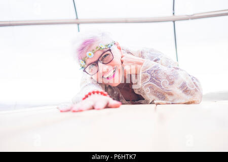 caucasian aged senior lady smile and enjoy lay down in a bright studio full of white light. nice mature female happy looking at the camera with fashio - Stock Photo