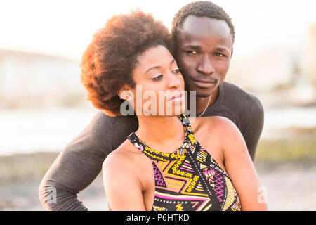 happy black race african couple at the beach in love and enjoying the leisure activity together sitting near the ocean coast summer time and loves vib - Stock Photo