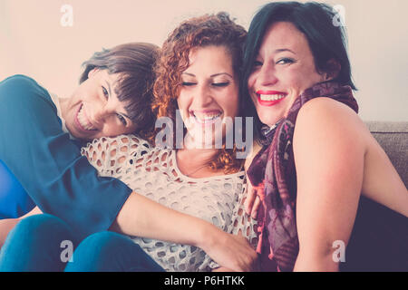 cheerful females middle age young womane friends together sitting on a sofa at home in leisure activity indoor. smile and enjoy the day hugging and to - Stock Photo