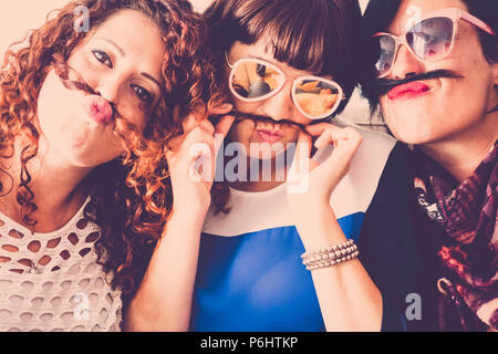 three caucasian females friends stay together in friendship and craziness using hair like moustache and happiness relationship concept. vintage full c
