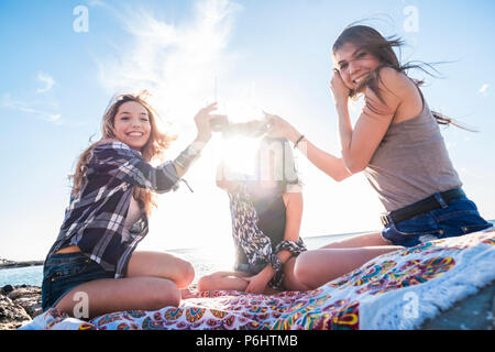 group of young women friend drinking together a fruit juice on a rock beach in Tenerife. Relationship for a team to enjoy the vacation and happiness.  - Stock Photo