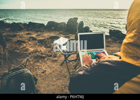 man at work in alternative office using laptop and smartphone to connect with internet and share things with the office. traveler concept digital noma - Stock Photo