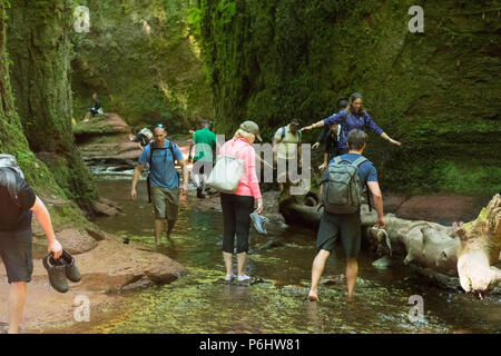 Tourists at Finnich Glen, Stirlingshire, Scotland - a beauty spot coming under increased pressure due to being used as a film location in Outlander - Stock Photo