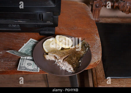 Cooked fish with lemon on a plate and us dollars on a table top, indoor still life - Stock Photo