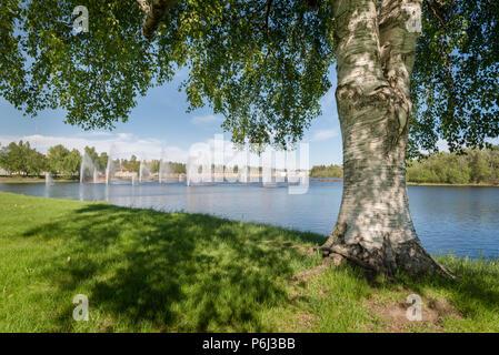 Fountains in Oulu, Finland seen from island called Lammassaari - Stock Photo