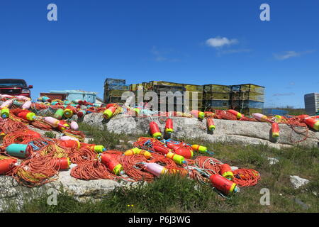 The multi-coloured buoys, nets, ropes and lobster traps make a colourful scene at the fishing village of Peggy's Cove on Nova Scotia's Bluenose Coast - Stock Photo