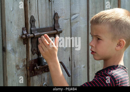 Young blond cute boy trying to open rusty slide bolt lock on lit by sun closed old wooden barn door. Children curiosity, love for adventures, safety,  - Stock Photo