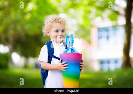 Happy child holding traditional German candy cone on the first school day. Little student with backpack and books excited to be back to school. Beginn - Stock Photo