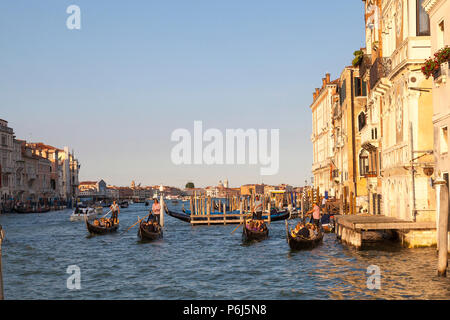 Tourists enjoying romantic  gondola rides at sunset on the Grand Canal, Venice, Veneto, Italy. Golden hour with reflections. - Stock Photo