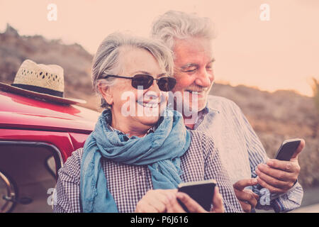 Elderly couple with hat, with glasses, with gray and white hair, with casual shirt, on vintage red car on vacation enjoying time and life. With a chee - Stock Photo