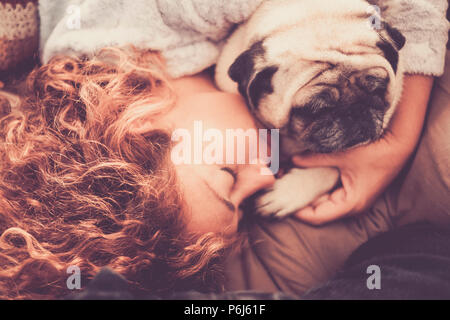 real true love between middle age beautiful woman caucasian sleeping and protect, her best friends dog pug. friendship and relationship at home in the - Stock Photo