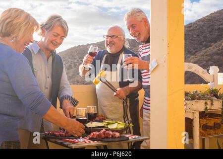 four active senior retired have fun in the terrace at home cooking some bbq everybody smiles and stay together in friendship under a nice sunny day.   - Stock Photo