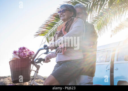 elderly senior caucasian couple play and enjoy leisure activity outdoor in lifestyle vacation. man and woman retired go on a vintage bike like childre - Stock Photo