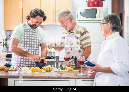 caucasian family three man people cook together lokking the how to do on the mobile phone of the mother. everybody have fun and laugh preparing someth - Stock Photo