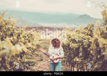 nice beautiful caucasian woman walk alone in the vineyard green background singing an ukulele acoustic guitar. freedom alternative lifestyle hippy con - Stock Photo