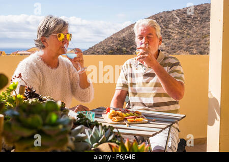 senior adult couple outdoor on the rooftop drinking somw white wine and eating some snacks food salds and fruits. sunny day of vacation or retired lif - Stock Photo