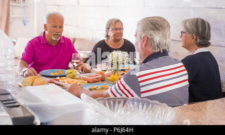 senior adult at home have lunch together in friendship and happiness. all serious speaking about problems and issues. two women and teo men for two fa - Stock Photo