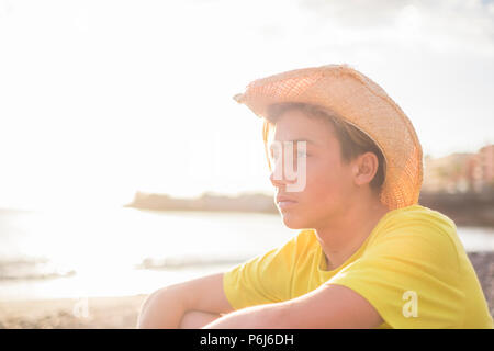 young beautiful boy 15 years old sitting on the beach in vacation looking at the horizon. ocean waves and sunset in backlight background. - Stock Photo