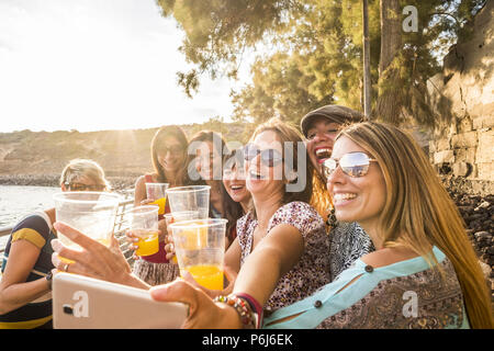 group of young beautiful caucasian woman taking selfie in vacation leisure activity outdoor near the beach and the ocean. sunset time with backlight a - Stock Photo