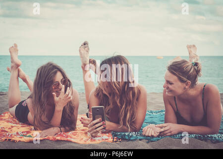 three nice girls use mobile phone technology to take pictures at the beach relaxing and enjoying lifestyle and vacation leisure. outdoor modern activi - Stock Photo