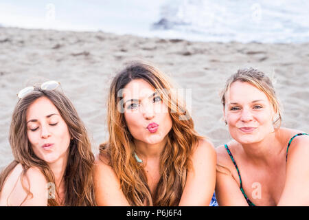 young women in friendship at the beach laying on the sand. sunny day and beautiful girls face expressions staying together enjoying the days of summer - Stock Photo