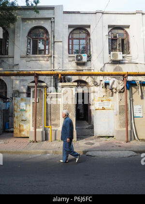 Tianjin, China - September 2017: Old man wearing traditional clothing walking in the French concession in the city center of Tianjin - Stock Photo