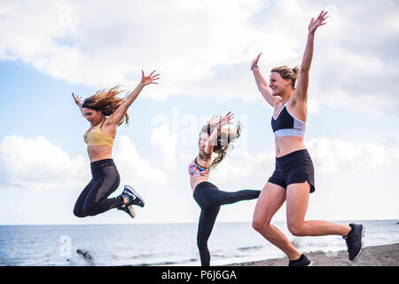 three beautiful bodie cacuasian girls jumping on the beach doing fintess workout. outdoor leisure sport activity for group of females people with ocea - Stock Photo