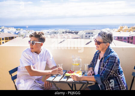 couple young and old people woman and boy grandmother and nephew for family concept lifestyle leisure activity eating something on the terrace rooftop - Stock Photo