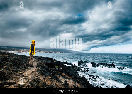 man with yellow jacket in a wild place on the ocean coast looking the power of the waves in a bad weather. challenge and enjoying the travel lifestyle - Stock Photo