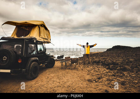 adventurer man in journey travel with off road car and roof tent to enjoy freedom and explorer concept. discover the world living near the power of th - Stock Photo