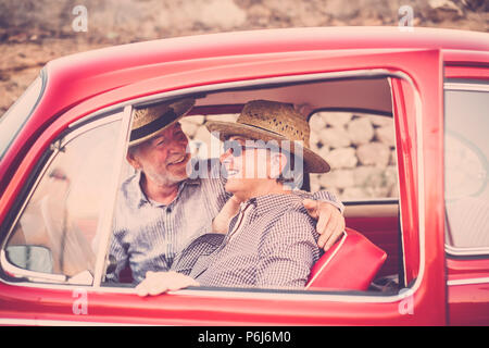 Nice beautiful couple of senior adult people inside an old red vintage car enjoy and stay together in outdoor travel leisure activity. Married and for - Stock Photo
