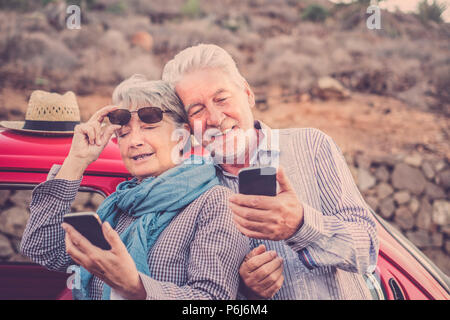Beautiful man and woman couple senior mature use smartphone outdoor in leisure activity checking internet for emails and friends to contact. vacation  - Stock Photo
