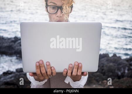 surprised face expression for beautiful caucasian young woman work on a laptop in alternative office outdoor on the coastline near the ocean waves. di - Stock Photo