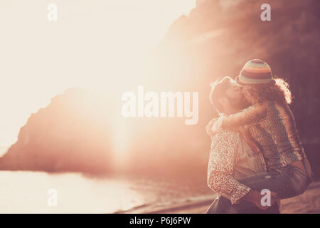 middle age caucasian couple kissing on the beach during an amazing golden warm sunset with ornage and red colors. hugging and carrying with passion an - Stock Photo