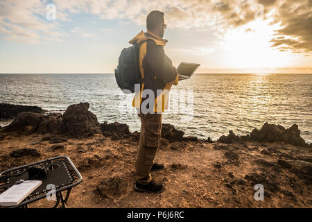 Digital nomad traveler man at work lokking an amazing golden sunset on the ocean. camera and laptop and beautiful lifestyle in outdoor leisure activit - Stock Photo