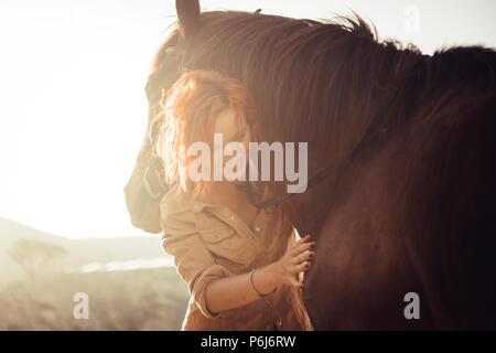 real love and friendship concept between nice beautiful caucasian lady and amazing horse. sunset time and backlight. sweetness and tenderness in horse - Stock Photo