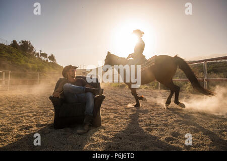 riders with horses in the golden sunset light. a man sitting on an old seat and a woman ride around him making dust. scenery image with windmills in b - Stock Photo
