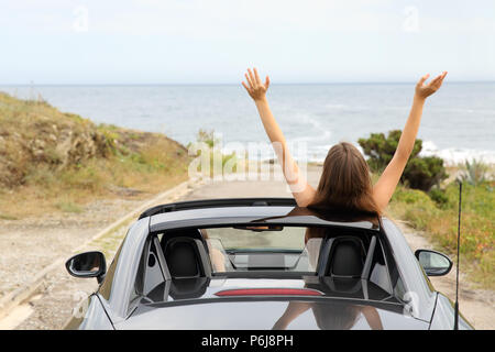 Back view portrait of two happy tourists driving a convertible car on vacation - Stock Photo